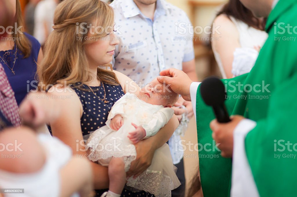 Mother hold baby on ceremony of child christening in church stock photo