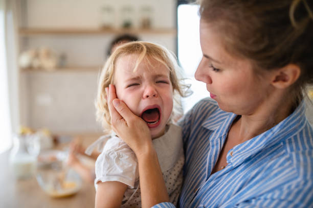 A mother holding a crying toddler daughter indoors in kitchen. stock photo