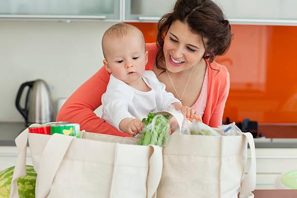 mutter holding baby und entladen lebensmittel - babytasche stock-fotos und bilder