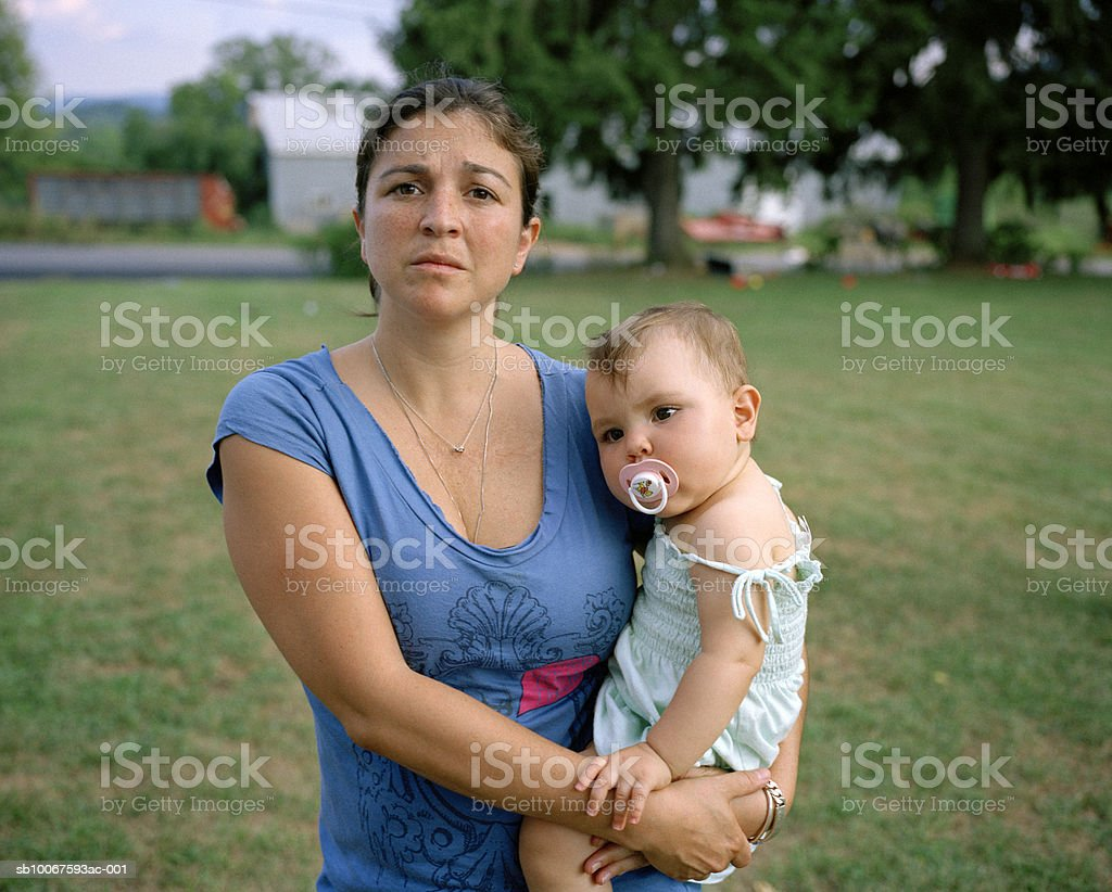 Mother holding baby girl (15-18 months) in lawn, portrait royalty-free stock photo