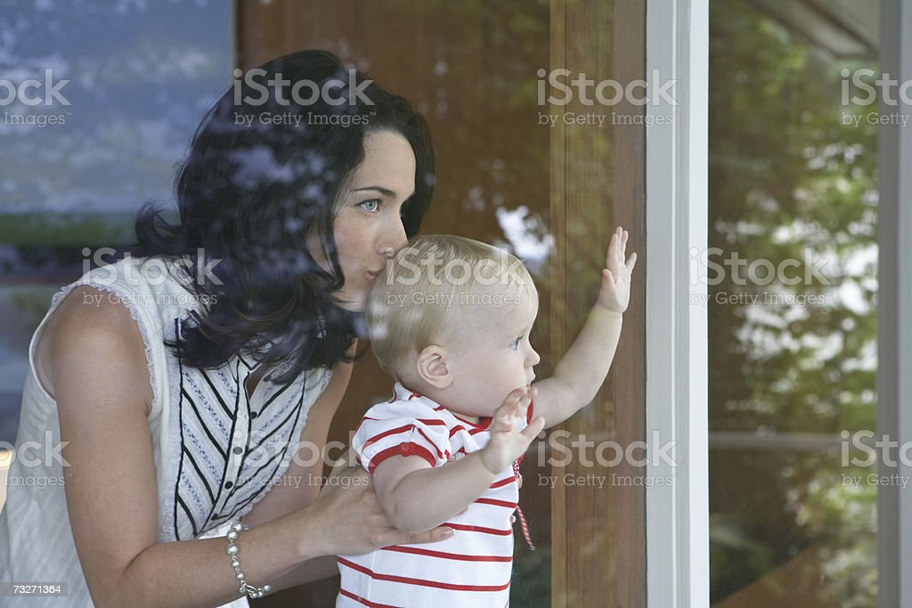 Mother holding baby girl (9-12 months) to window royalty-free stock photo