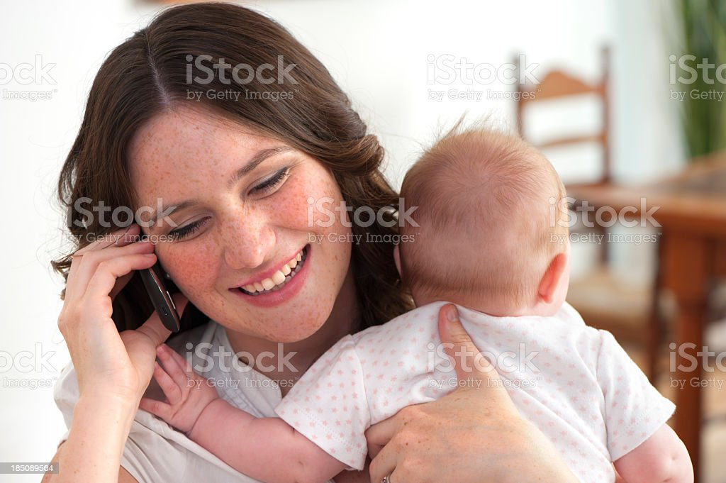 mother holding baby while talking on phone royalty-free stock photo