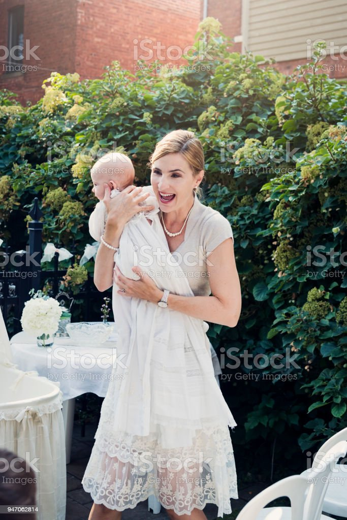 Mother holding baby with traditionnal baptism robe. stock photo