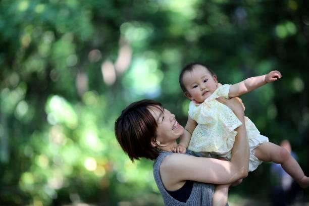 媽媽抱著身體在春天公園圖像檔