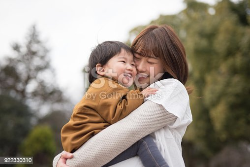 istock Mother holding child in arms 922330310