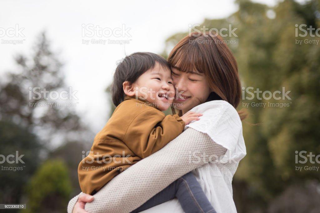 母親の腕の中で子を保持 ストックフォト