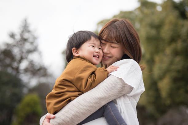 母親の腕の中で子を保持 - 子供時代 ストックフォトと画像