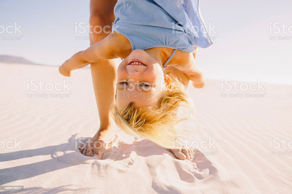 Mother holding her daughter upside down