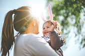 Mother holding child with bunny ears