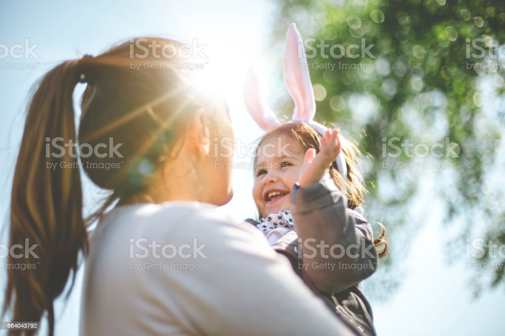 Mother holding child with bunny ears stock photo