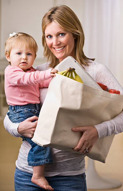Mother Holding Daughter and Groceries stock photo
