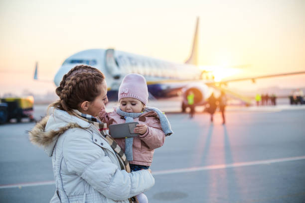 Mother holding daughter at the airport stock photo