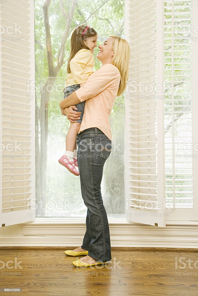 Mother Holding Daughter in Front of Open Window royalty-free stock photo