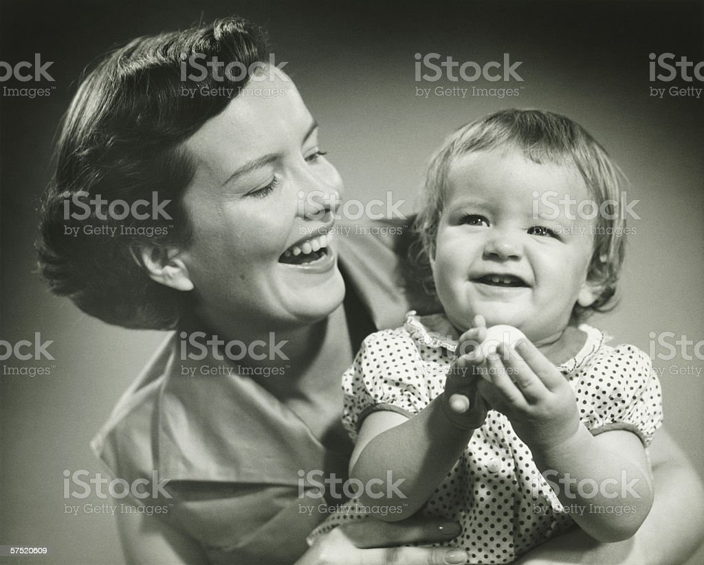 Mother holding daughter (2-3) in studio, (B&W), portrait royalty-free stock photo