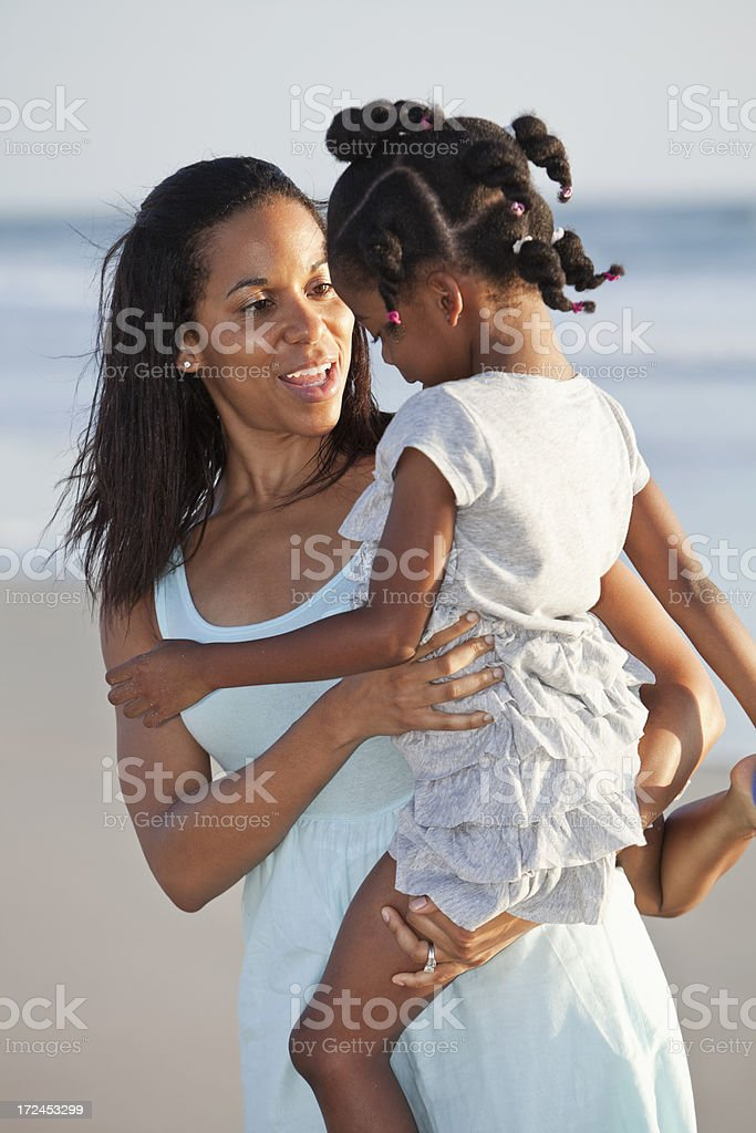 Mother holding daughter on beach stock photo