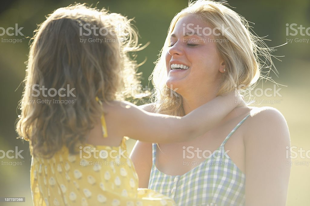 Mother holding daughter outdoors stock photo