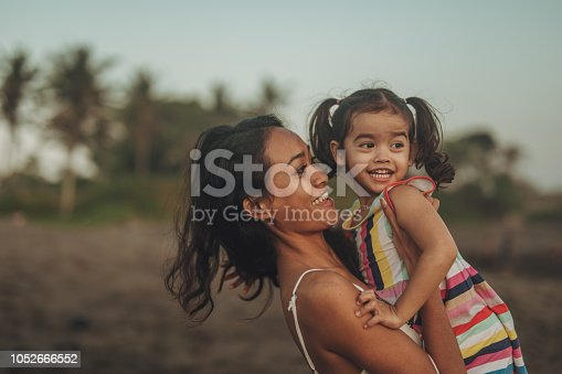 Mother and daughter relaxing on the beach together, mother holding daughter.