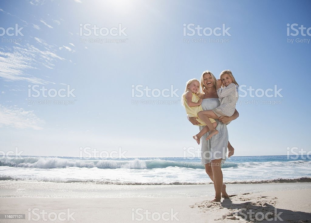 Mother holding daughters on beach royalty-free stock photo