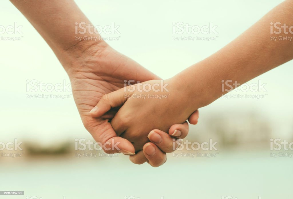 Mother holding hand of her daughter. stock photo