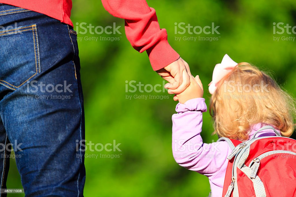 Mother holding hand of little daughter outdoors stock photo