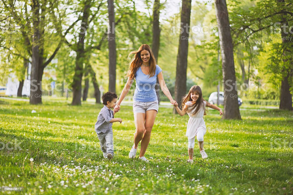 Mother holding hands and running with her children outdoors. royalty-free stock photo