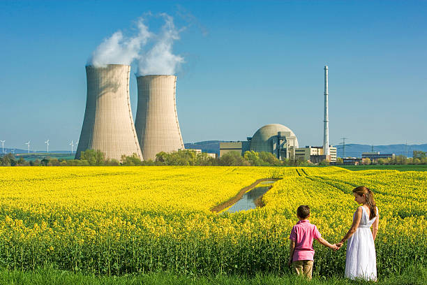 Mother Holding Hands with Son at Nuclear Power Station Rear view on Young mother holding hand of her son looking concerned at him in front of flowering canola field and nuclear power station. Some small wind turbines in the background on the left side of the two cooling towers. Useful as symbol for future and energy questions.  nuclear power station stock pictures, royalty-free photos & images