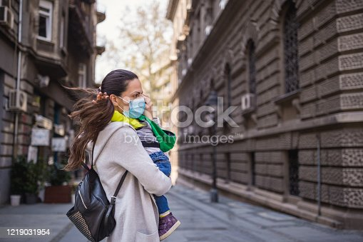 Mother holding her baby boy wearing protective mask. She is scared. Belgrade, Serbia