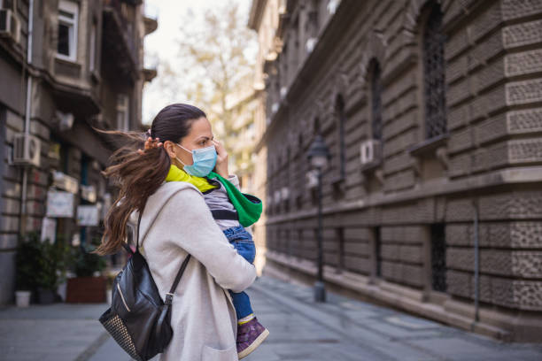 Mother holding her baby boy wearing protective mask stock photo