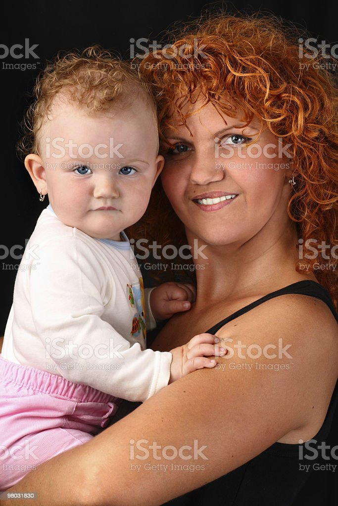 Mother holding her baby daughter isolated on black background royalty-free stock photo