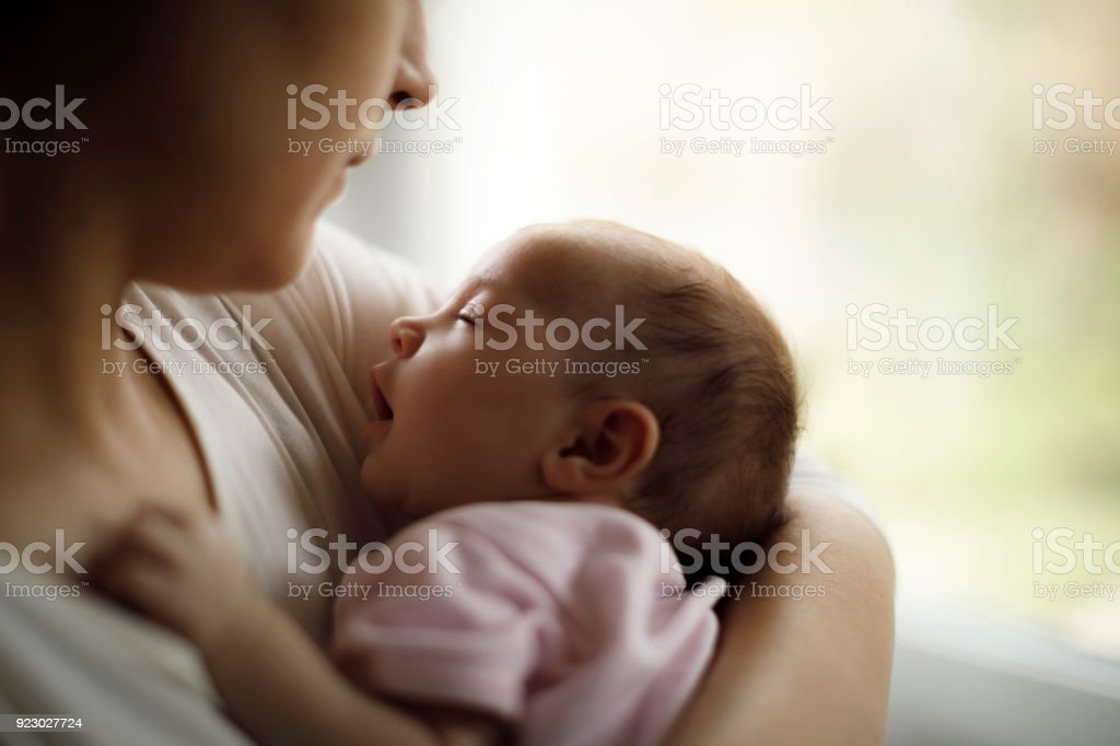 Mother holding her baby girl at home stock photo