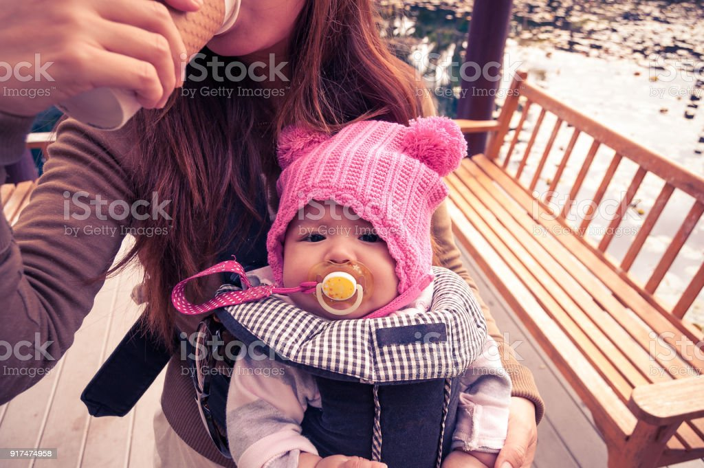 Mother holding her baby girl in baby carrier while drinking coffee stock photo