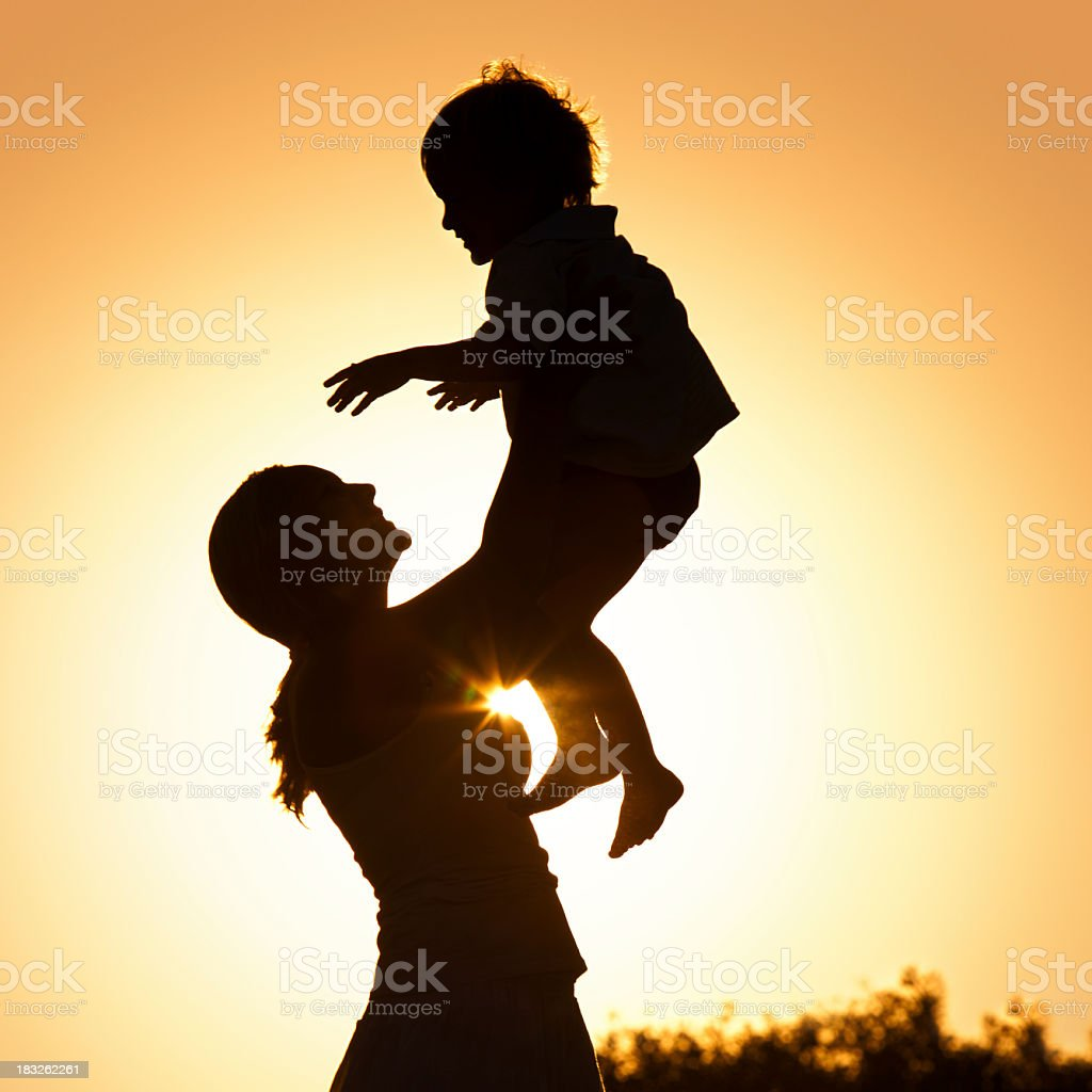 Mother holding her child at sunset royalty-free stock photo