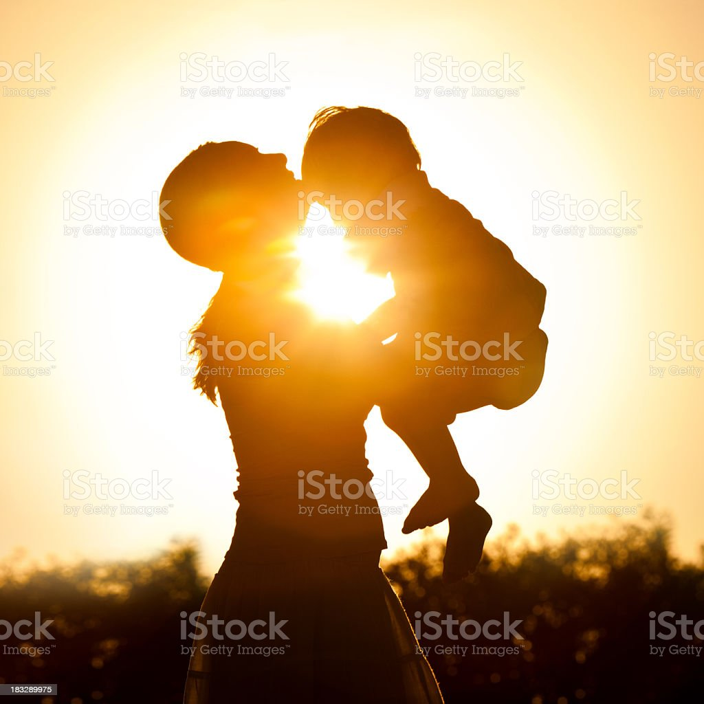 Mother holding her child at sunset stock photo