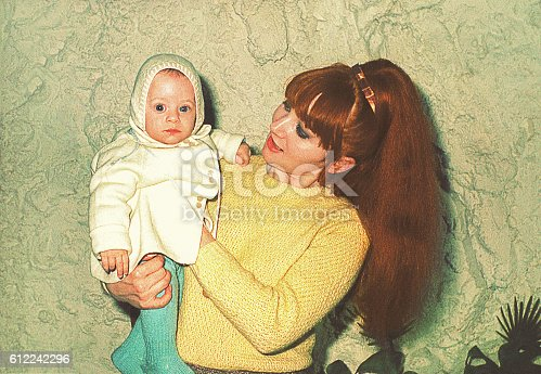 Vintage photo form the sixties of a mother holding her cute little baby