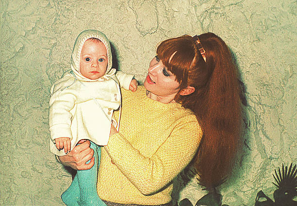 mother holding her cute little baby - 1960s style stock photos and pictures