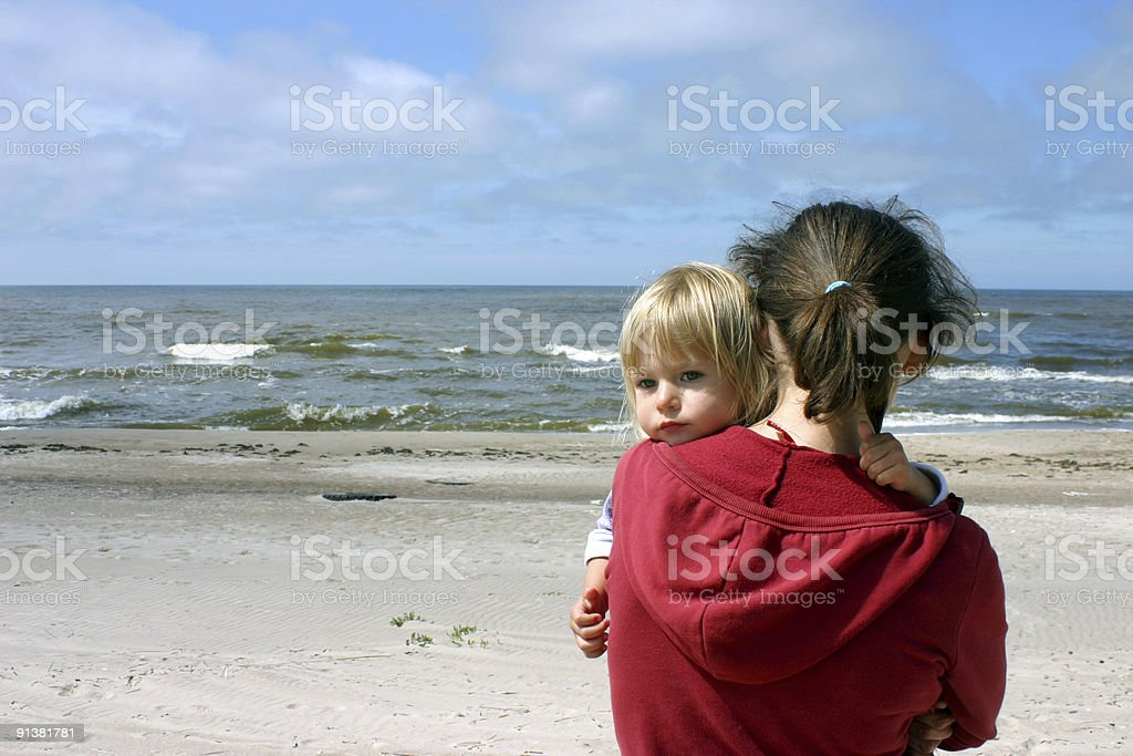 Mother holding her daughter at the beach on a sunny day royalty-free stock photo