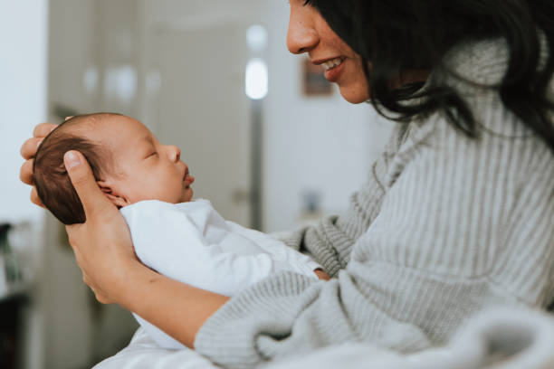 Mother holding her infant baby stock photo