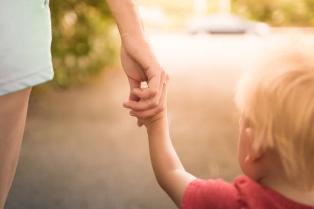 Mother holding her little boys hand walking down the street. stock photo