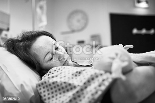 Black and white shot of mother holding her newborn baby right after delivery