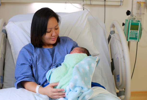 mother holding her newborn child after labor - c section stock photos and pictures