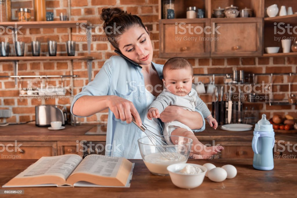 mother holding her son, talking on smartphone and mixing a dough stock photo