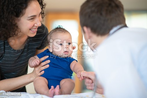 A mother holds her son in her arms while a male doctor gives him a checkup.