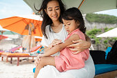 mother holding his daughter when give a sunblock to doughter's arm on the beach