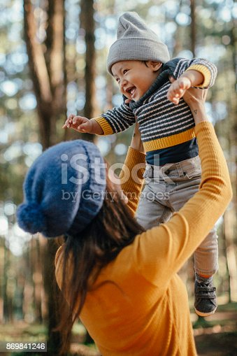 istock Mother holding his son in forest in sunset. 869841246