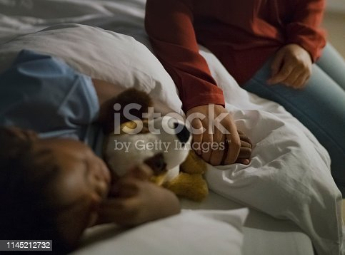 Midsection of woman holding son's hand sleeping on hospital bed. Ill boy is with stuffed toy relaxing by mother at ward. They are at children's hospital.