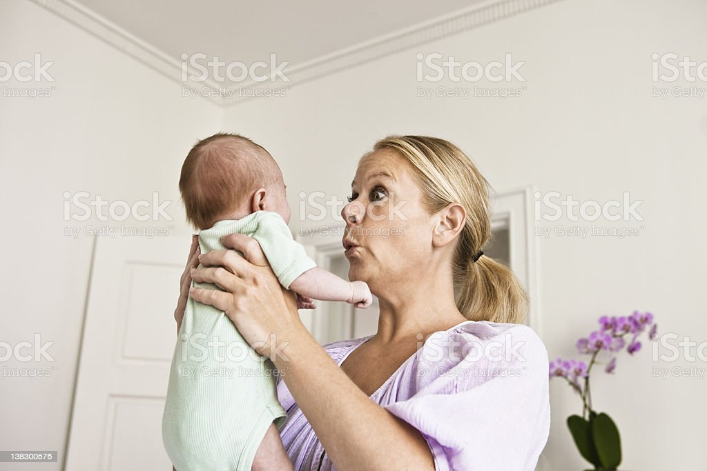 Mother holding infant in bedroom stock photo