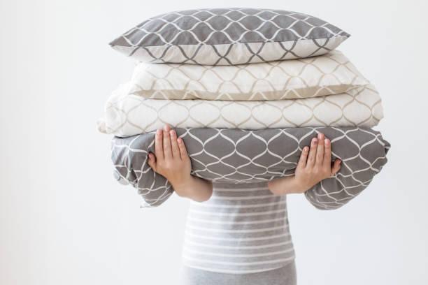 Mutter hält moderne Beige und grau Bettwäsche Haufen, Kinder Zimmer Bett, weiße Wand Hintergrund im Trend, Minimalismus reinigen Wohnkonzept – Foto