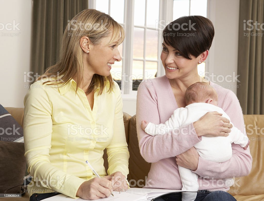 Mother Holding Newborn Baby Talking With Health Visitor At Home stock photo