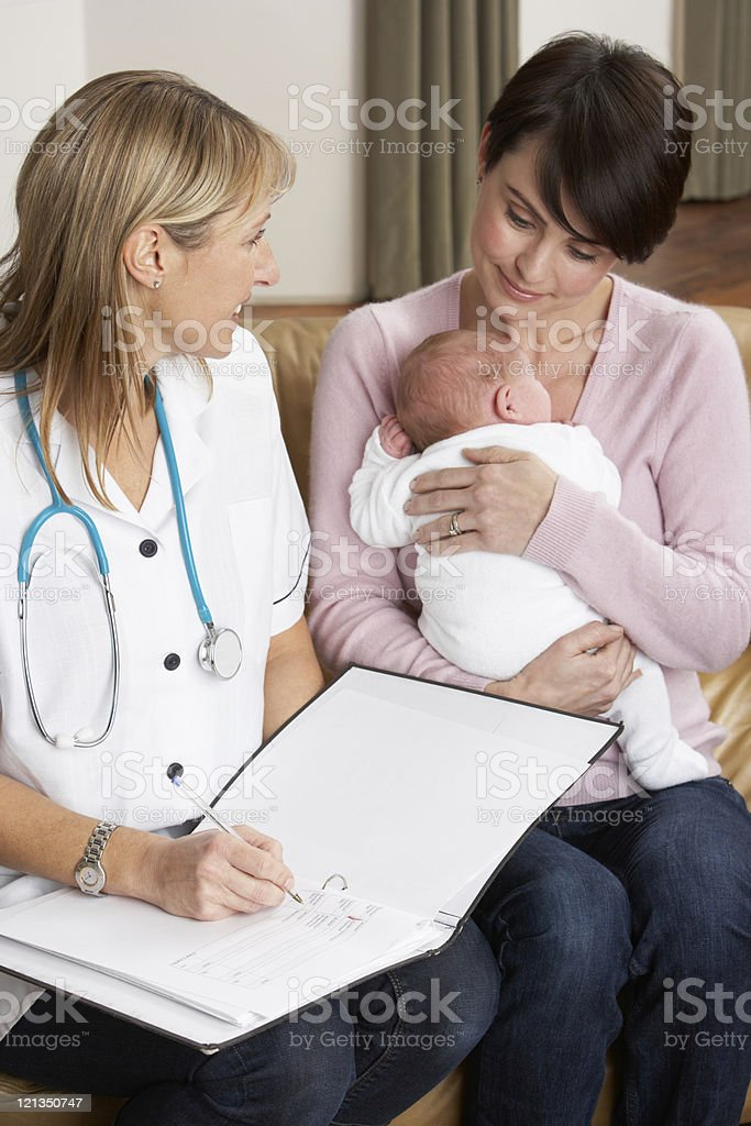 Mother Holding Newborn Baby Talking With Health Visitor stock photo