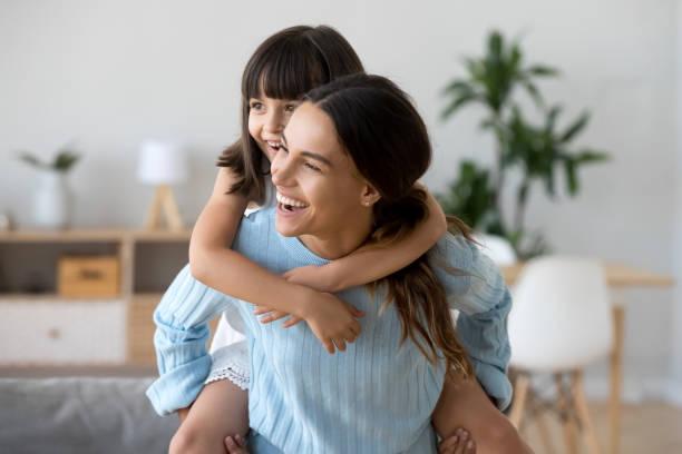 madre sosteniendo espalda pequeña hija tocando juntos en casa - niñera fotografías e imágenes de stock